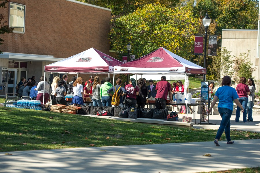 Students gathering around free giveaway tent by student center